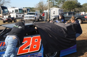 Dennis Erb, Jr. and crew member Heather Lynne push their car into place.