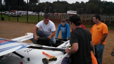 Joron Horton at work atop his Warrior Race Car as Mike Nuchols and other crew members look on.